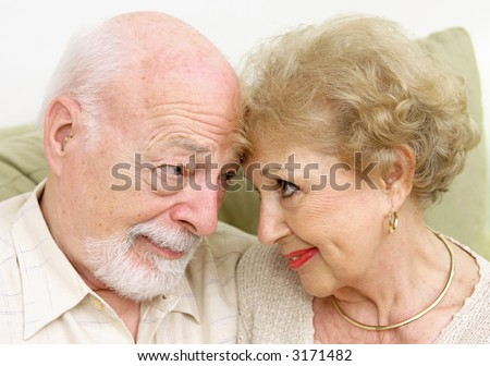 A senior couple looking at each-other lovingly nose to nose. - stock photo
