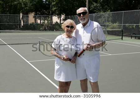 A senior couple on the tennis courts wearing sunglasses and getting ready for a game. - stock photo