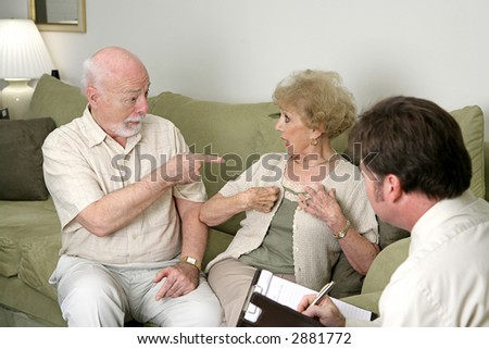 A senior couple seeking marriage counseling.  He's pointing at her and she's looking surprised.  Focus on husband. - stock photo