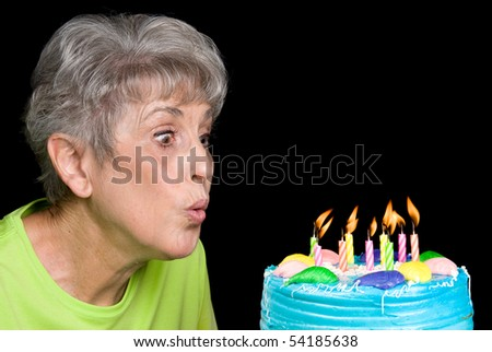 A senior female blows out candels on a cake.  Ideal for birthday, anniversary or any other celebration inference. - stock photo