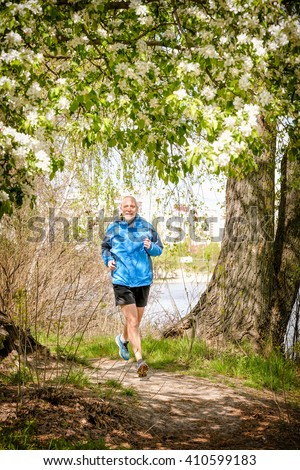 A senior man dressed in black and blue is running in the forest, close to the lake, under an apple blossom, during a warm spring day - stock photo