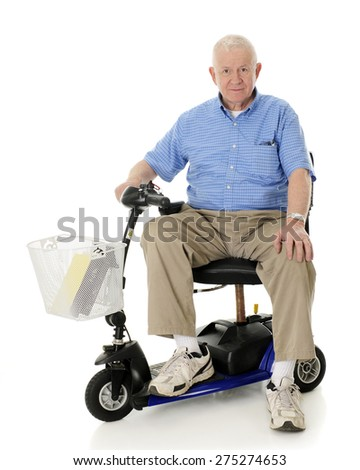 A senior man happily looking at the viewer from his electric scooter.  On a white background. - stock photo