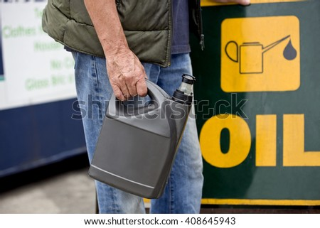 A senior man holding an oil container in a recycling centre, close-up - stock photo