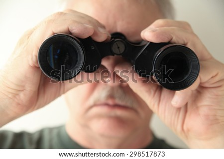 A senior man holds an old pair of binoculars pointed at the camera. - stock photo