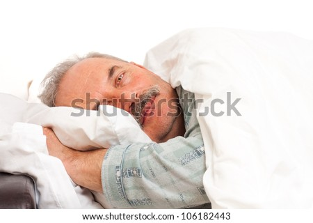 A senior man laying in bad. - stock photo