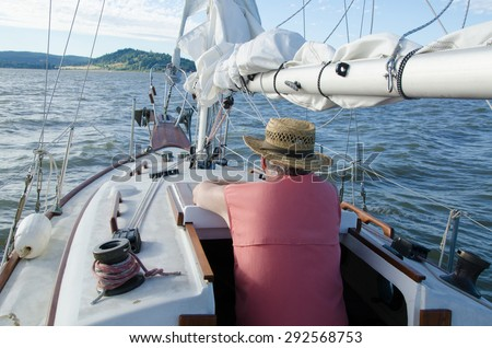 A senior man relaxes on board his classic ketch sailboat as he contemplates the distant shore. - stock photo