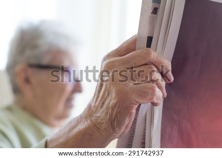 a senior person reading newspaper - stock photo
