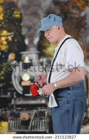 A senior train engineer smiling at the viewer as he removes an apple from his lunch pail.  On a white background. - stock photo