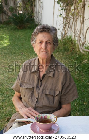 A senior woman between 70 and 80 years old  is reading a book in the garden of private old people's home. - stock photo