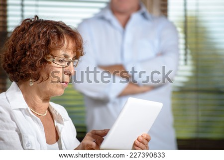 a senior woman in a sofa with a digital tablet - stock photo