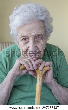 a senior woman leaning on cane - stock photo