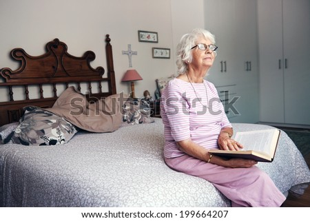 A senior woman reading her book in her bedroom and looking up - stock photo