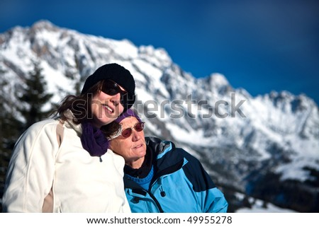 A senior woman with her daughter in a beautiful winter setting in the mountains. - stock photo