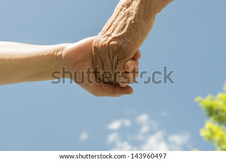 A senior women and daughter holding hands under a blue sky. - stock photo
