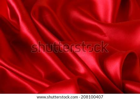 A sensual closeup of a wavy sheet of red satin. - stock photo