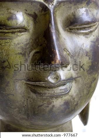 A serene bronze Buddha's face - stock photo
