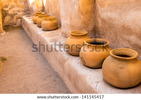 A series of Mexican clay pots on an adobe shelf at Mission Tumacacori, Arizona - stock photo