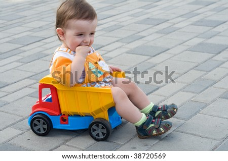 a serious baby boy is sitting in the toy truck - stock photo