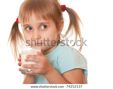 A serious girl is holding a glass of milk in her hands; isolated on the white background - stock photo