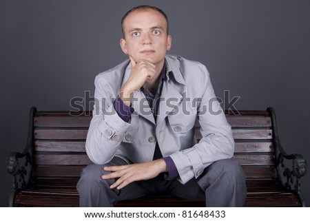 a serious guy in a gray cloak sitting on the bench, thinking - stock photo