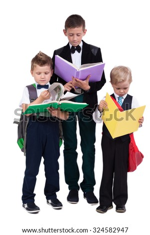 a serious high school student and two kids with backpacks on a white background reading books, picture with depth of field - stock photo