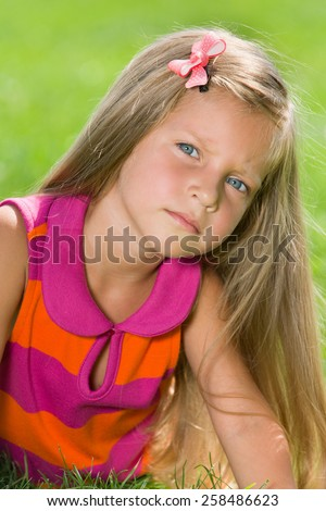 A serious little girl is lying on the green grass in a summer day - stock photo