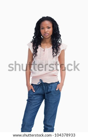 A serious young woman is standing with her hands in her pocket - stock photo