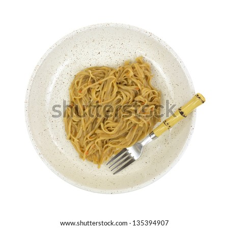 A serving of Szechuan noodles in a shallow bowl with a bamboo motif fork on a white background. - stock photo