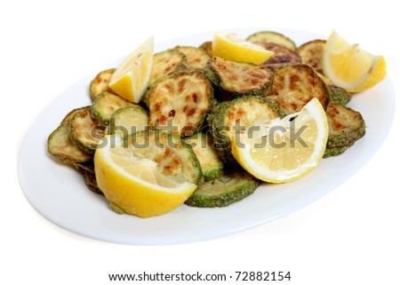 A serving plate of fried courgette rings with lemon wedges, isolated on white - stock photo
