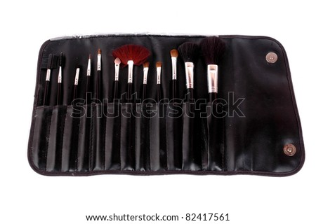 a set brush for makeup in black leather bag isolated on white background - stock photo