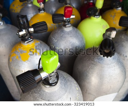 A set of air tanks that have been prepared for a diving expedition. The focal point is on the green cap of the closest tank and the others recede into the background. - stock photo