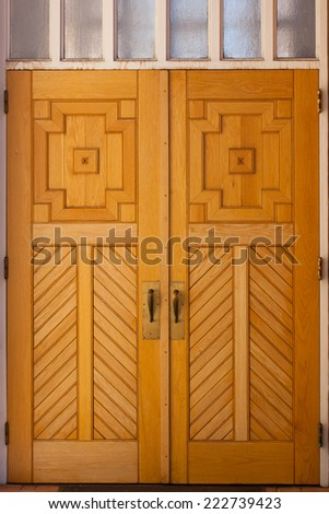 A set of antique wooden church doors on the back side of the church  showing the craftsmanship of the builders. - stock photo