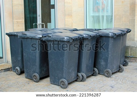A set of black bins ready for rubbish and recycling  - stock photo