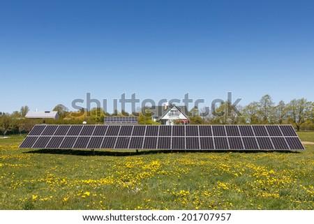 A set of dark blue solar panels in a grass field - stock photo