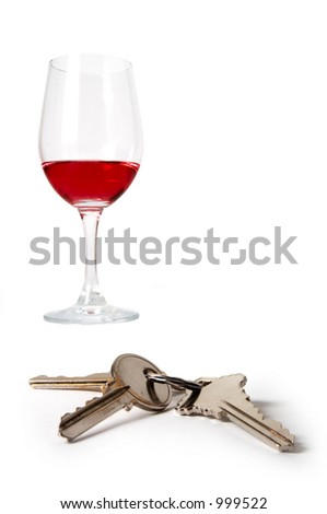 A set of keys in front of a wine glass symbolizing drinking and driving. - stock photo