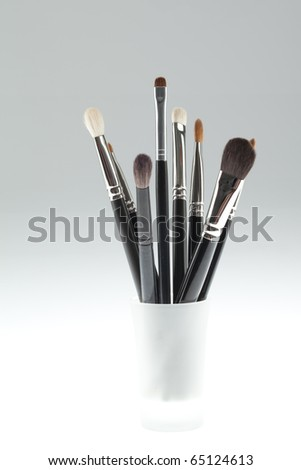 a set of make-up brushes, shot on a white background, arranged in a small white glass - stock photo