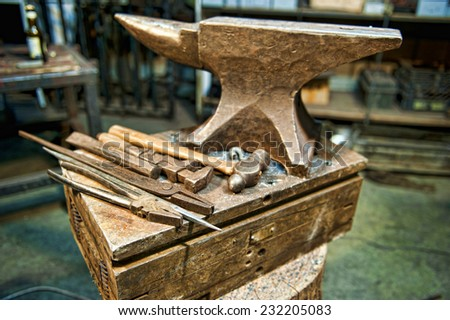 A set of metal fabrication tools along side an anvil in a metal fabrication shop. - stock photo