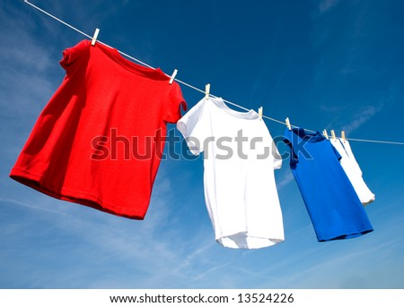 a set of red, white and blue T-shirts hanging on a clothesline on a beautiful, sunny day, add text or graphic to shirts or copy space.  Independance day or USA theme. - stock photo
