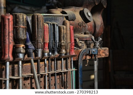 A set of screwdrivers, saws, vice, and other work tools in an old workshop - stock photo