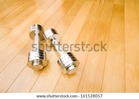 A set of stainless steel free weights shining on an all wood floor. - stock photo