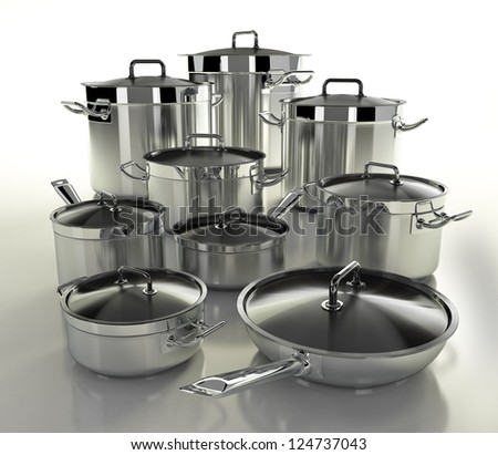 A set of stainless steel pans on a light background - stock photo