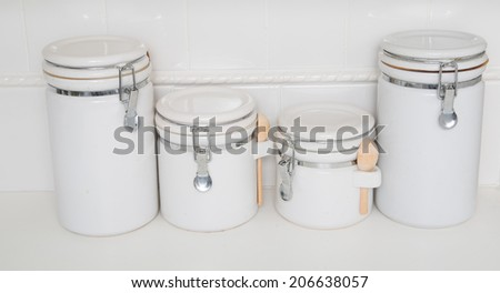 A set of white and chrome ceramic canisters on a white countertop with white tile - stock photo