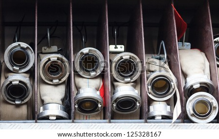 A set of white firehoses on a truck of a voluntary fire brigade - stock photo