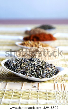 A set of white plastic spoon with different spicery - dried basil, ground ginger, mustard grains, ground paprika and cinnamon, on a straw table-bedding, closeup, blur background, vertical - stock photo