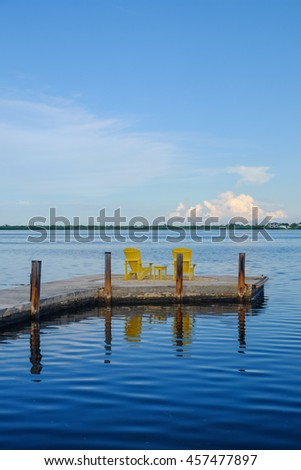 A set of yellow adirondack chairs sit at the end of a wooden and concrete in the florida keys at the end of the beautiful sunny day on vacation - stock photo