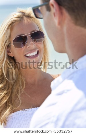A sexy and attractive man and woman couple wearing sunglasses and having romantic fun laughing in the sunshine at the beach - stock photo