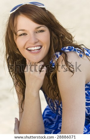 A sexy and beautiful young brunette woman sitting at the beach happily laughing with golden sand behind her - stock photo