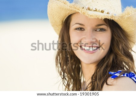 A sexy and beautiful young brunette woman sitting at the beach wearing a straw cowboy hat with golden sand and the sea behind her - stock photo