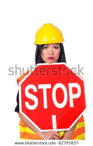 A sexy female construction worker frowns while holding a stop sign. - stock photo