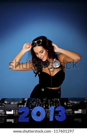 A sexy female DJ making music at a party to see 2013 in. Female sexy DJ. - stock photo